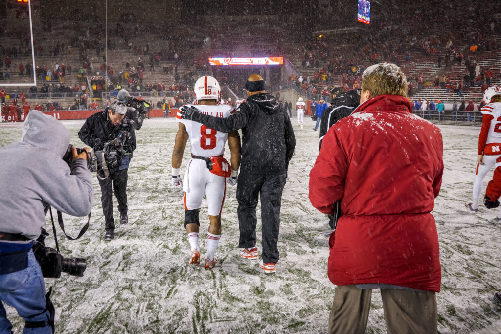 football player leaving field in snow